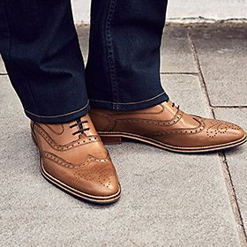 Man wearing tan brown smart shoes and jeans