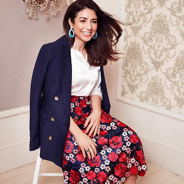 Lindy wears lace floral skirt, cream silk blouse and navy blazer