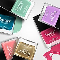 Different shades of Butter London nail polish against a colourful backdrop