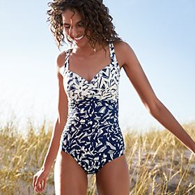 Woman on a beach wearing a printed swimsuit