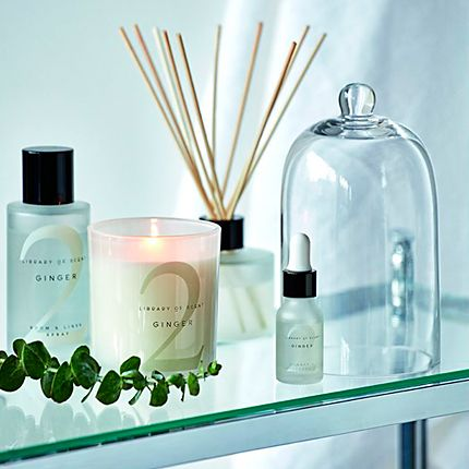 Scented candles, room sprays and a diffuser on a glass shelf