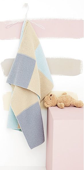Hanging checked baby blanket and teddy bear