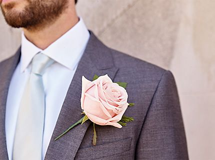 Close up of flower buttonhole and man wearing a wedding suit