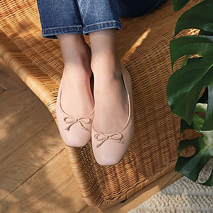 Woman sat on a wicker chair wearing blue jeans and nude-pink ballet flats