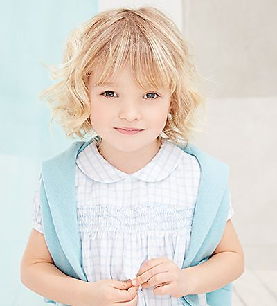 Girl wearing pale blue smock dress and merino cardigan