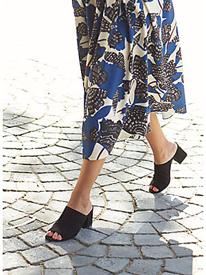 Woman modelling mules and printed skirt