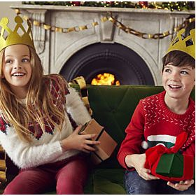 Girl and boy wearing Christmas jumpers and paper crowns