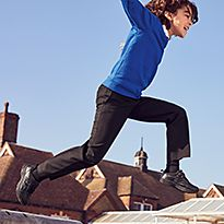 Boy leaping in the air wearing M&S school uniform