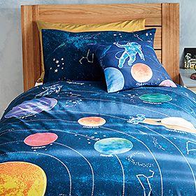 Space-print children's bedding set on wooden bed