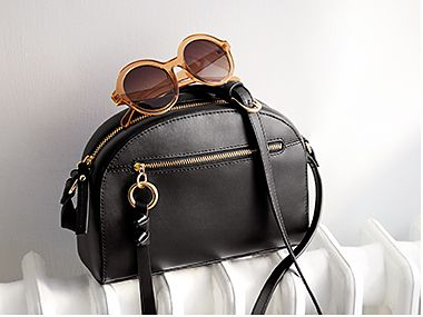 Black handbag on a radiator with sunglasses resting on top