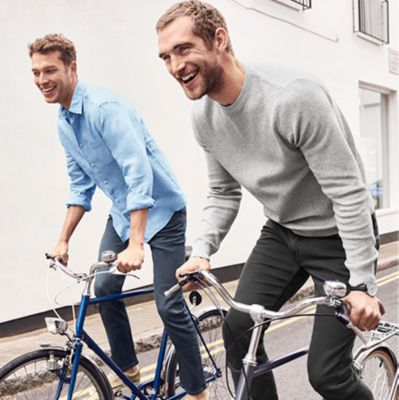 Two men wearing mens jeans and casual clothes riding bikes