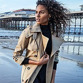 Woman on a beach wearing a beige trench coat