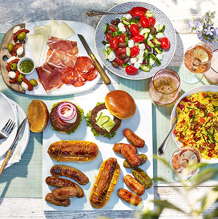Table laid with barbecue food and salad