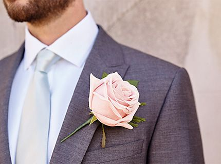 Man in grey wedding suit with floral on lapel