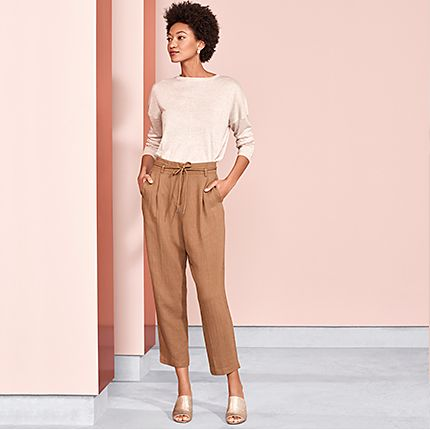 Woman in pink top and brown trousers
