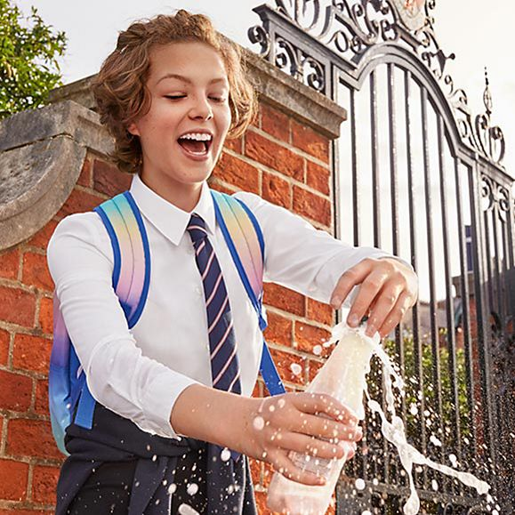 Girl in school uniform skirt and shirt opening drink bottle