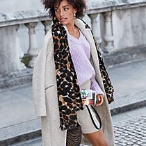 Women wearing an overcoat with a jumper and patterned scarf