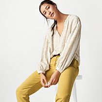 Woman wearing a beige printed blouse and mustard cotton chinos