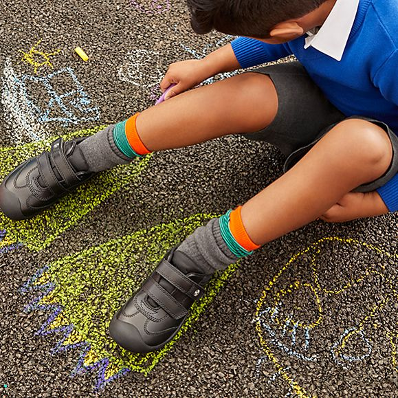 Child wearing M&S school uniform sat on the ground using chalk to draw round his feet