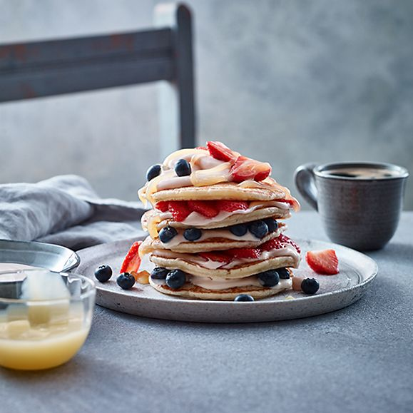 A stack of gin-and-tonic pancakes with strawberries and blueberries
