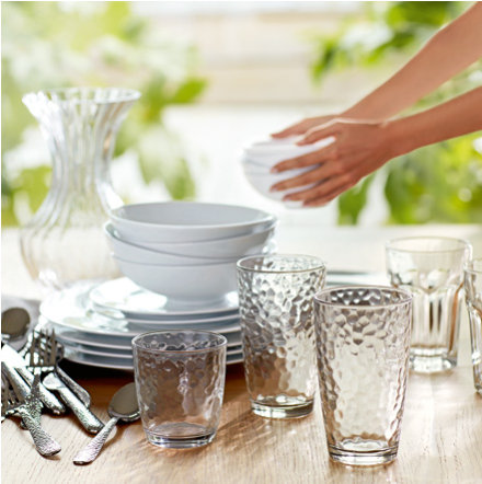 Woman placing crockery, cutlery and glassware on a wooden dining table