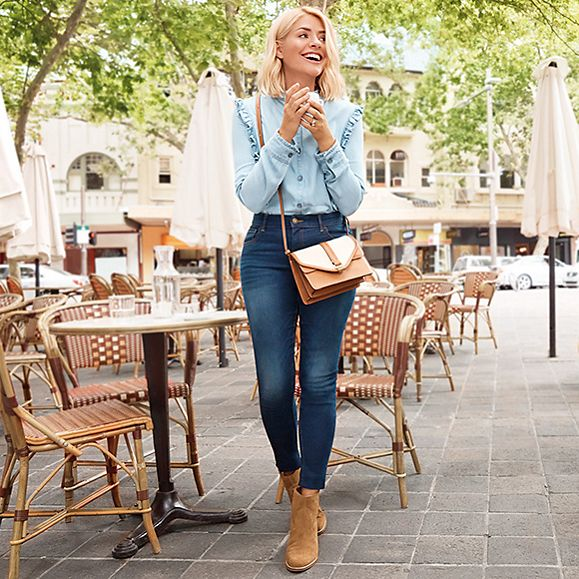 Holly Willoughby wearing a blue frill-detail denim shirt and blue skinny jeans