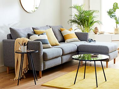 Grey corner sofa with cushions in living room