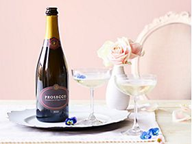Bottle of prosecco on a tray with champagne coupes and flowers
