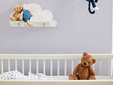 Teddy sitting in a baby's cot