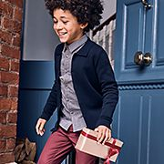 Boy wearing a navy cardigan, blue shirt and red trousers holding a Christmas gift