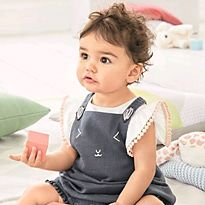 Baby girl wearing a white top and navy pinafore dress playing with building blocks