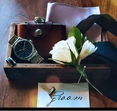 Box containing groom's watch, flask, cufflinks, tie, handkerchief and buttonhole