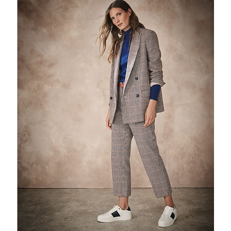 Woman wearing checked trouser suit with trainers