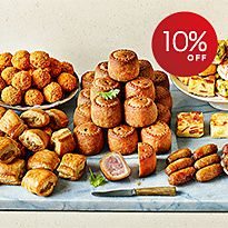 Party food selection with pork pies, quiche, and sausage rolls