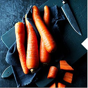 Whole and chopped carrots on a cutting board with a knife