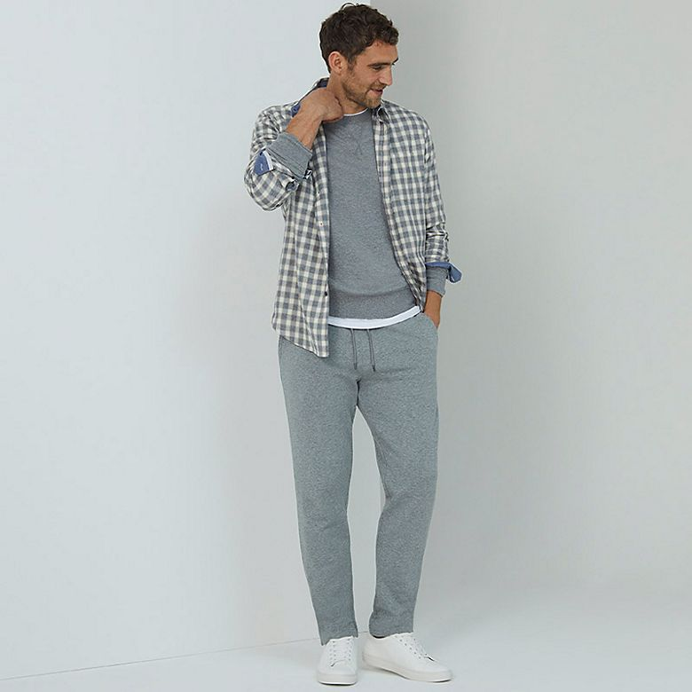 Man wearing checked shirt with grey sweatshirt and joggers