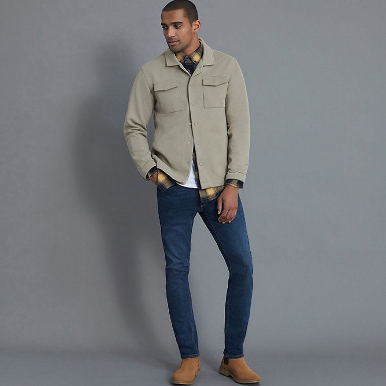 Man wears beige jacket, white T-shirt, light blue jeans and tan boots