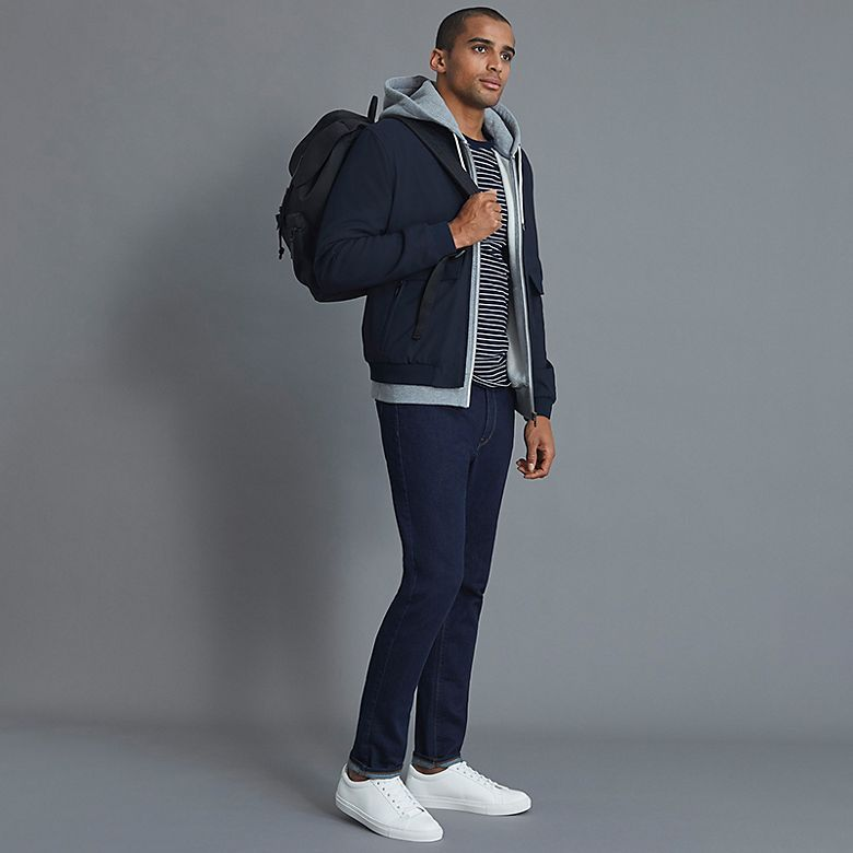 Man wears navy coat with light blue hoodie and navy trousers
