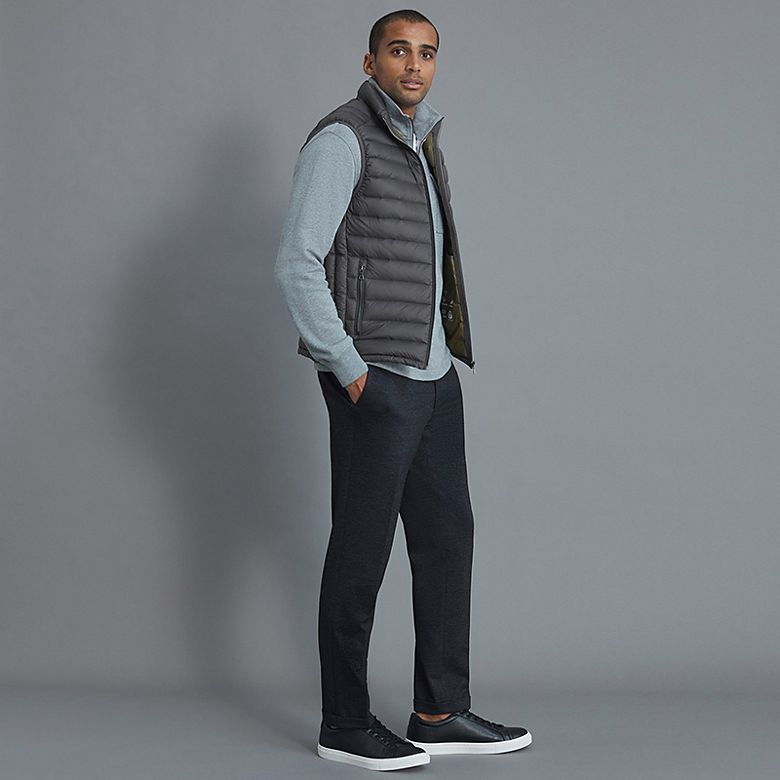 Man wears grey gilet over light blue top and jeans