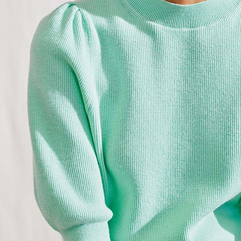 Woman wearing turquoise jumper with pleated sleeves