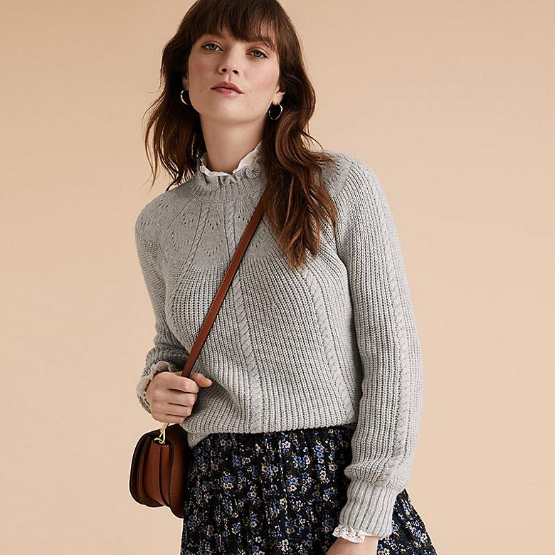 Woman wearing grey jumper over white blouse with floral skirt carrying a leather shoulder bag