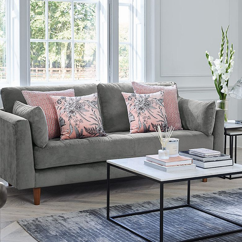Living room with grey sofa, pink cushions, marble-effect coffee table and nest of tables