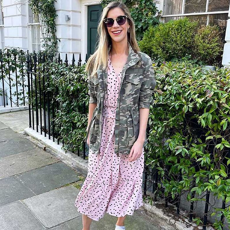 Woman wearing camo jacket and pink polka-dot dress