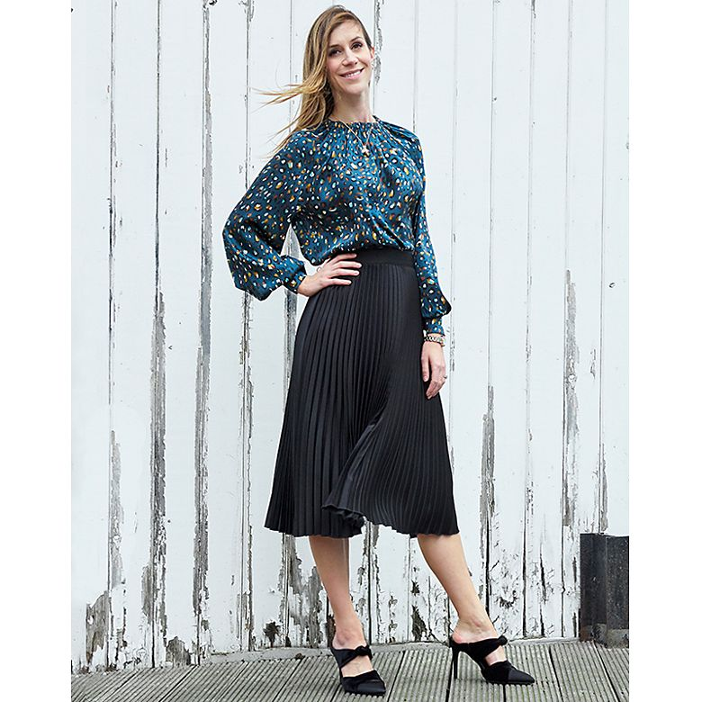 Woman wears blouse and skirt from Holly's Must-Haves collection