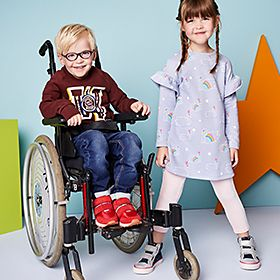 Little boy in wheelchair wearing brown tops and girl in lilac dress