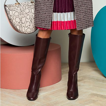 Model wears knee-high boots with a pleated skirt and tweed coat