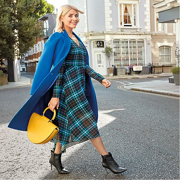 Holly Willoughby wearing a cobalt coat, navy checked dress, black ankle boots and a yellow tote bag