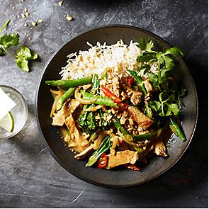 A bowl of pork Thai stir-fry with fresh vegetables and rice