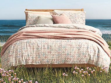 Bed with pastel-coloured printed bedding