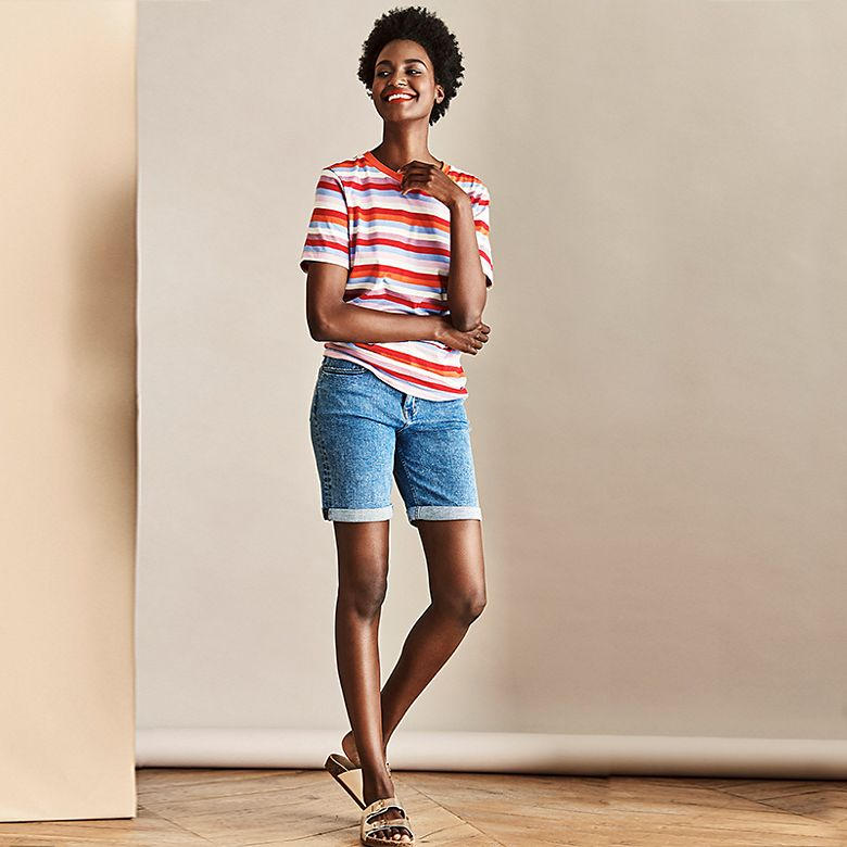 Woman wearing mid-rise denim shorts with multicoloured striped T-shirt and metallic sliders